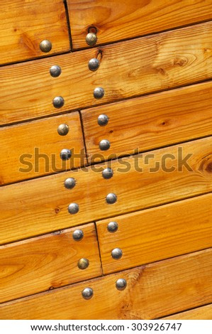 Detail of a lacquered wood surface of a boat with nails for background