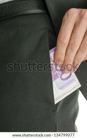 Detail of a male hand putting five hundred Euro banknotes in pocket on  pants of a suit.