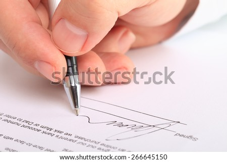 Detail of a male hand signing a contract - stock photo