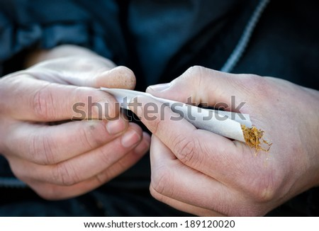 Detail of a man�´s hands rolling a cigarette. - stock photo