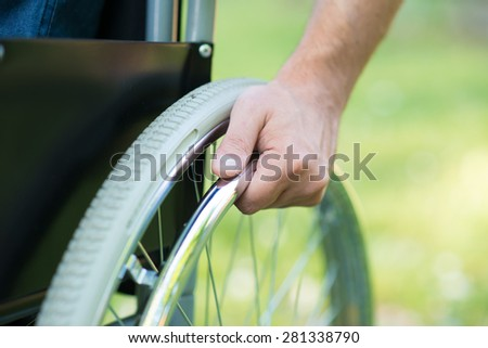 Detail of a man using a wheelchair in a park - stock photo