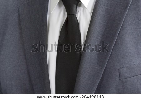Detail of a man wearing a suite with white shirt and black tie - stock photo