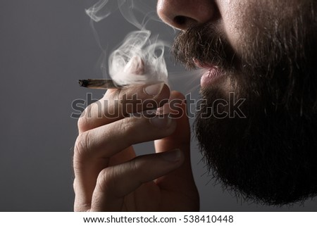 Detail of a Man with a Beard Smoking a Cigarette