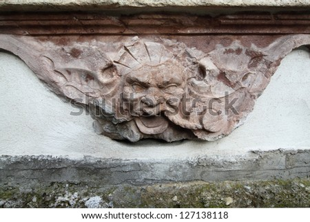 Detail of a marble tombstone - demonic mask - stock photo