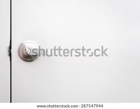 Detail of a metallic knob on white door background - stock photo