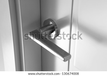 Detail of a metallic knob on white door horizontal - stock photo
