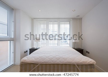 detail of a modern and bright bedroom with double bed and two bedside tables and lamps - stock photo