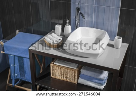 detail of a modern bathroom with sink and accessories, bathroom cabinet and blue bathroom tiles - stock photo