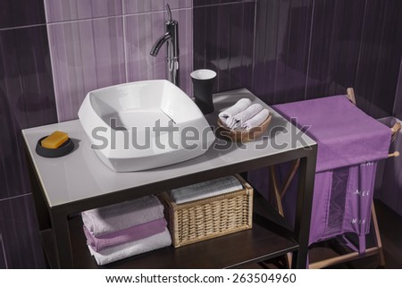 detail of a modern bathroom with sink and accessories, bathroom cabinet and purple bathroom tiles - stock photo