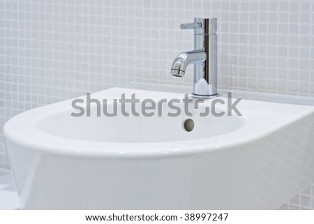 detail of a modern ceramic hand wash basin with chrome water mixer tap - stock photo
