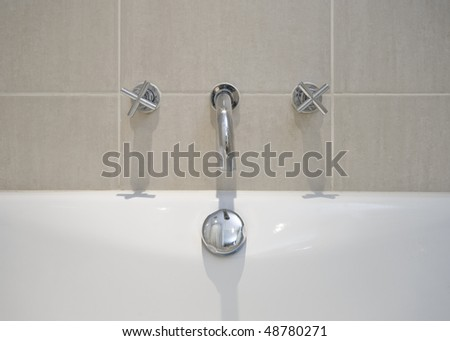 detail of a modern designer water mixer tap over bath tub - stock photo