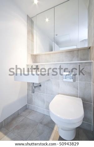 Detail of a modern en suite bathroom with ceramic toilet, wash basin in beige - stock photo