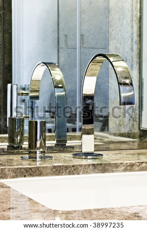 detail of a modern marble top hand wash basin with chrome water mixer tap - stock photo