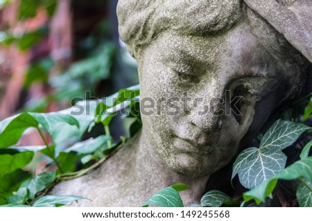 detail of a mourning sculpture on a cemetery - stock photo
