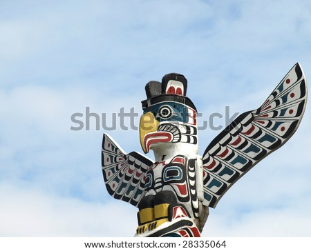 Detail of a North American Totem Pole against a blue sky - stock photo