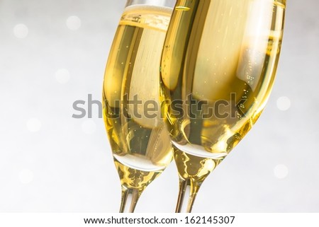 detail of a pair of flutes of golden champagne on silver bokeh background