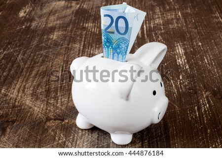 Detail of a piggy bank and twenty euro banknote - stock photo