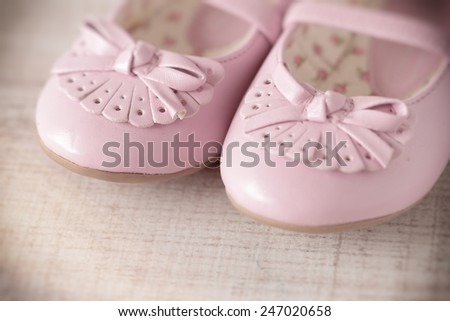 Detail of a pink girl shoes over wooden deck floor. Filtered image. - stock photo