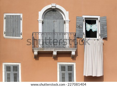 Detail of a pink wall with balcony and wooden windows - stock photo