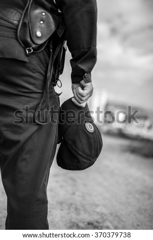 Detail of a police officer holding cap. Selective focus with shallow depth of field. Black and white toning.