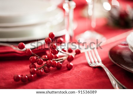 detail of a red holly berry decoration on a festive table setting - stock photo