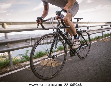 Detail of a road bike with a cyclist pedaling on a road. - stock photo