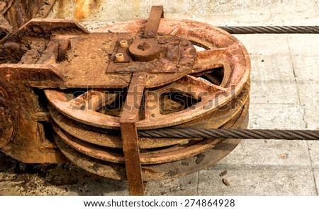 Detail of a rusty drag metal wheel with its cable of a old shipyard ramp disused - stock photo