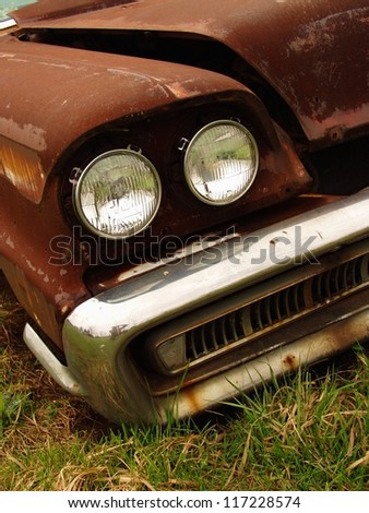 Detail of a rusty old abandoned car - stock photo