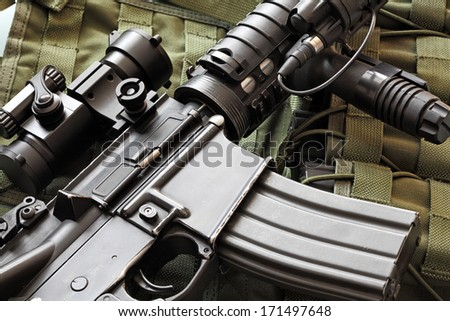 Detail of a scratched M4A1 (AR-15) carbine and green military tactical vest - stock photo