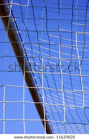 detail of a soccer post and net over a blue sky
