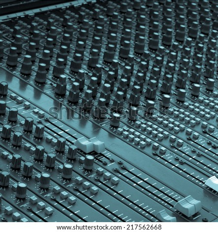 Detail of a soundboard mixer electronic device - cool cyanotype - stock photo