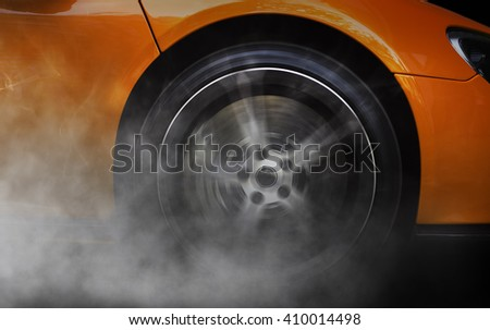 Detail of a sport car with spinning wheel, smoking, doing drifts and burnouts - stock photo