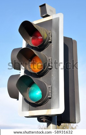 Detail of a Traffic Light on Green against a Blue Sky - stock photo