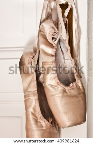 Detail of a used ballet pointe shoes hanging on a prewar door