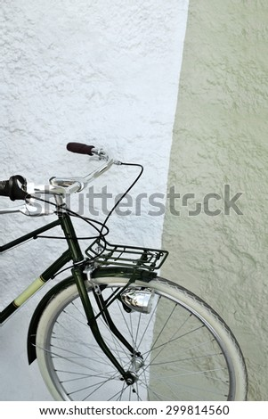 Detail of a vintage green and yellow bicycle against a wall - stock photo