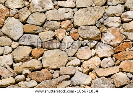 detail of a wall made with beige stone - stock photo