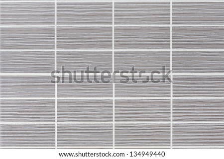 detail of a wall of gray rectangular tiles - stock photo