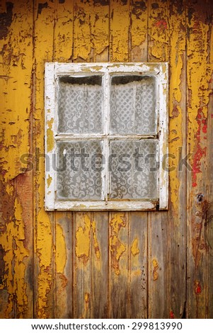 Detail of a weathered yellow wooden door with a small window - stock photo