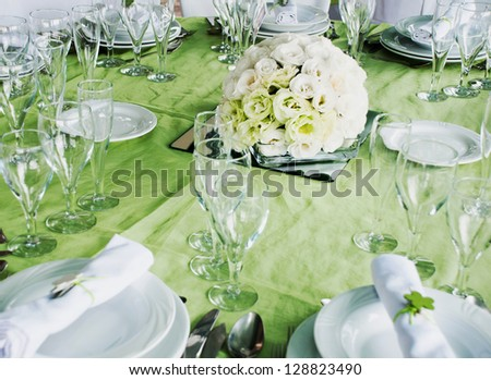 detail of a wedding table set for fine dining with estomas flowers arrangement - stock photo