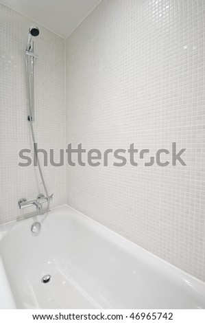 detail of a white ceramic bath tub with shower attachment and mosaic tiles