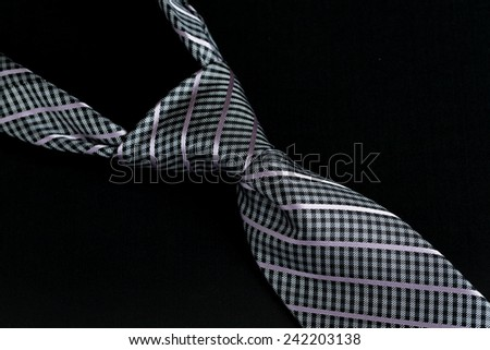 Detail of a windsor knot on gray and blue knotted tie isolated against black background - stock photo