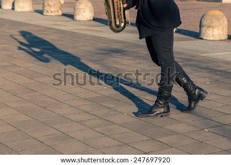 Detail of a woman posing in the city streets with her saxophone