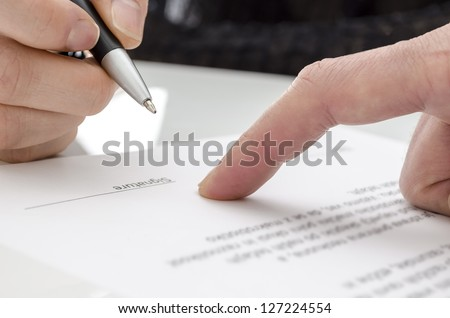 Detail of a woman signing a paper. Male finger showing where to sign. - stock photo