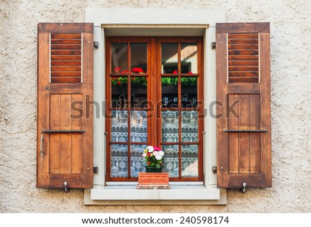 Detail of a wooden window with shutters open on stone wall - stock photo