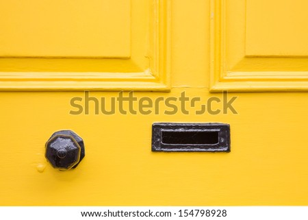 Detail of a yellow front door with black knob and letter box