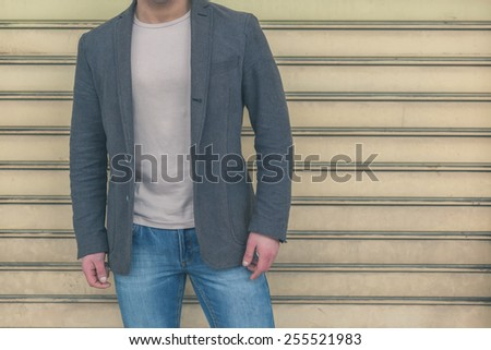 Detail of a young handsome man with jacket hair posing in the city streets