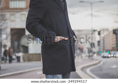 Detail of a young man with coat posing in the city streets