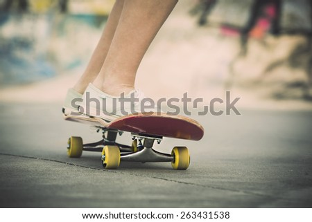 Detail of a young woman feet riding a skateboard - stock photo