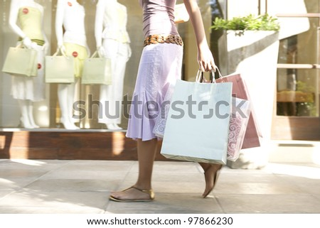 Detail of a young woman's body walking down a shopping street holding shopping bags.