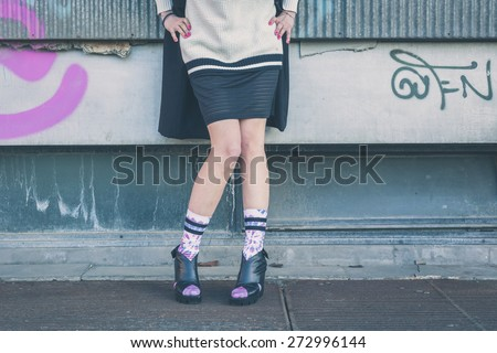 Detail of a young woman wearing wedge heels shoes posing in an urban context - stock photo